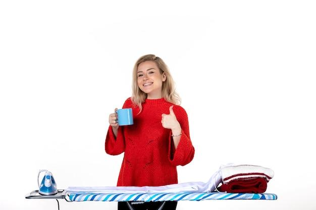 흰색 배경에 확인 제스처를 하는 파란색 컵을 들고 다림판 뒤에 서 있는 웃고 있는 매력적인 젊은 여성의 전면 모습 프리미엄 사진