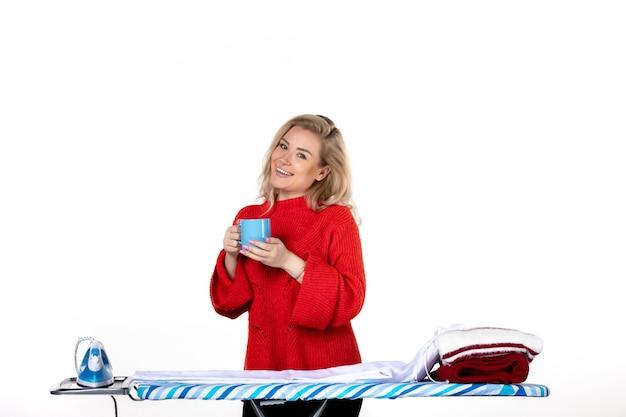 흰색 배경에 파란색 컵을 들고 다림판 뒤에 서 있는 웃고 있는 매력적인 젊은 여성의 전면 모습