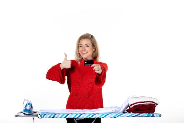 흰색 바탕에 확인 제스처를 하는 은행 카드를 보여주는 다리미판 뒤에 서 있는 웃고 있는 매력적인 여성의 전면 모습