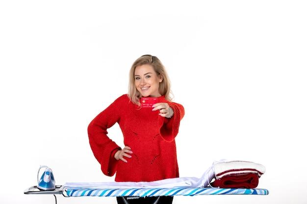 흰색 배경에 은행 카드를 보여주는 다리미판 뒤에 서 있는 웃고 있는 매력적인 젊은 여성의 전면 모습