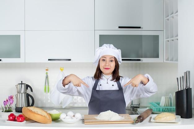 白いキッチンで彼女の制服を指している若い笑顔の女性シェフの正面図