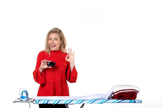 흰색 배경에 안경 제스처를 만드는 은행 카드를 보여주는 다리미판 뒤에 서 있는 웃고 있는 젊고 매력적인 여성의 전면 모습