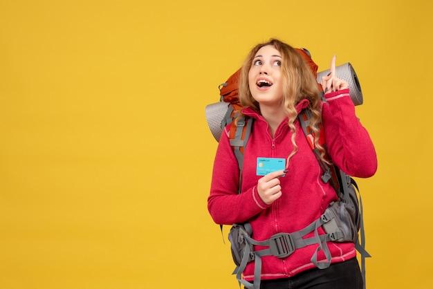 上向きの銀行カードを保持している彼女の荷物を収集する医療マスクで若い笑顔の旅行少女の正面