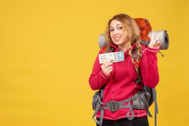 チケットを保持し、2つを示す医療マスクで若い笑顔の旅行の女の子の正面図