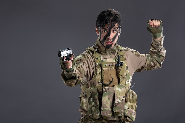검은 벽에 총을 조준 위장에 젊은 군인의 전면 보기