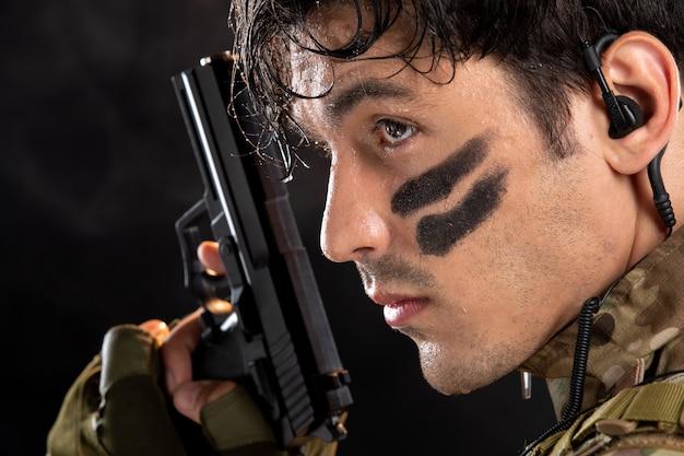 검은 벽에 총을 목표로 위장에 젊은 군인의 전면보기