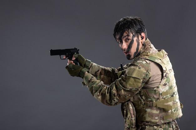 Вид спереди молодого солдата в камуфляже, направленного из пистолета на темный пол, палестинская танковая война