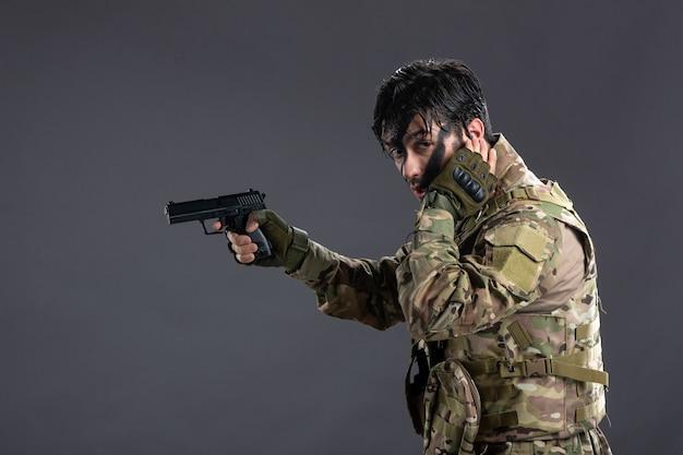어두운 벽에 총을 조준 위장에 젊은 군인의 전면 보기