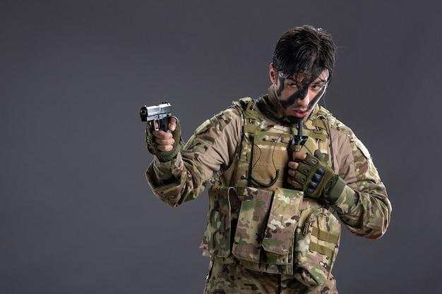 Вид спереди молодого солдата в камуфляже, направленного из пистолета на темную стену