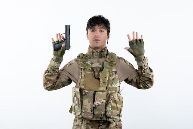 총 흰 벽으로 항복 위장에 젊은 군인의 전면 보기