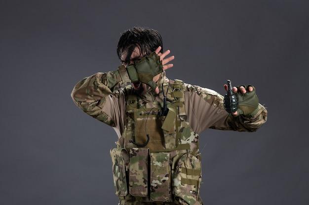 Вид спереди молодого солдата в камуфляже с гранатой на темной стене