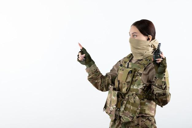 Вид спереди молодого солдата в камуфляже с гранатой белой стеной