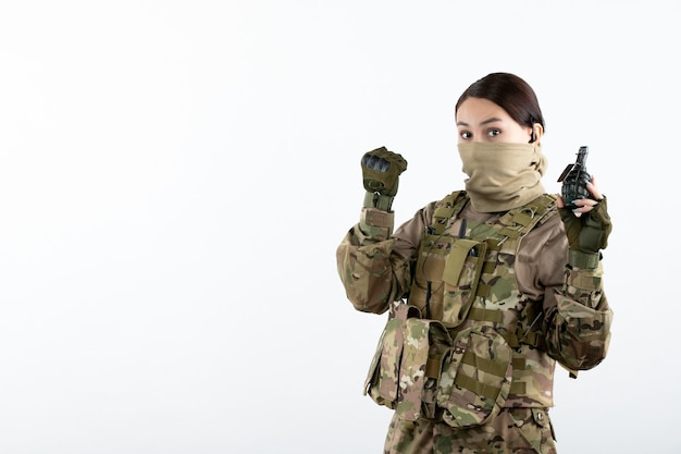 手榴弾の白い壁で迷彩の若い兵士の正面図