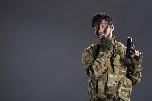 어두운 벽에 총을 든 위장을 한 젊은 군인의 전면 모습