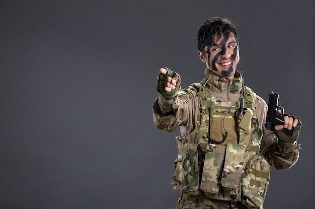 Вид спереди молодого солдата в камуфляже с пистолетом на темной стене