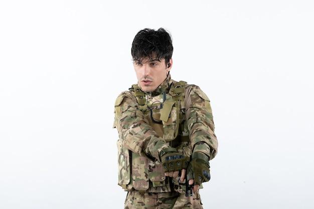 총 흰 벽으로 위장에 젊은 군인의 전면 보기