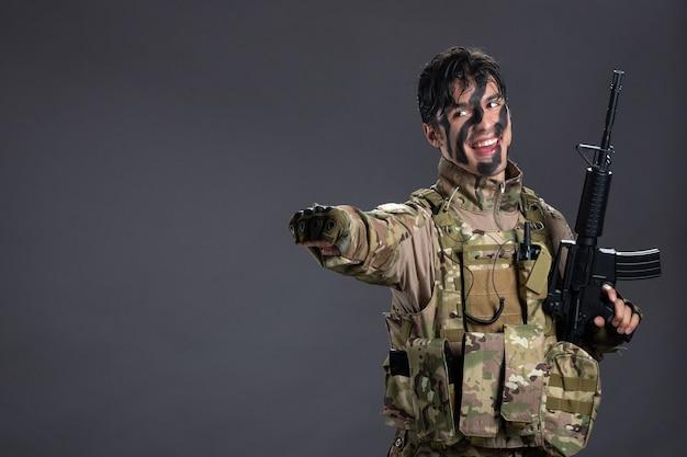 Вид спереди молодого солдата в камуфляже с пулеметом на темной стене