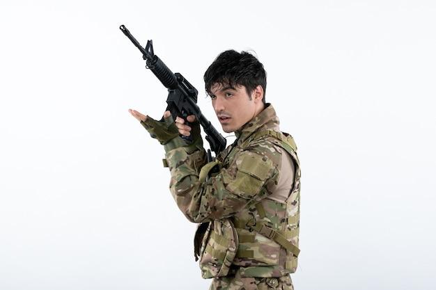 기관총 흰 벽으로 위장에 젊은 군인의 전면 보기