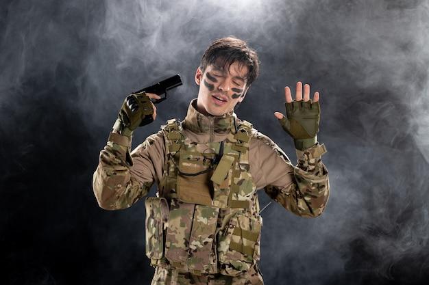 총 검은 연기가 자욱한 벽과 제복을 입은 젊은 군인의 전면보기