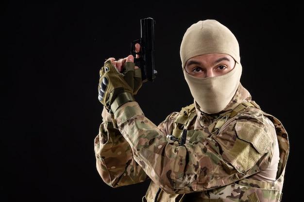 Вид спереди молодого солдата в форме с пистолетом на черной стене