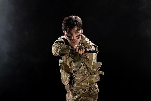검은 벽에 위장에 총을 든 젊은 군인의 전면 보기