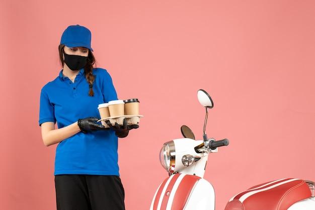 パステル ピーチ色の背景にコーヒーの小さなケーキを保持しているオートバイの隣に立っている医療マスク手袋を着た若い驚いた宅配便の女の子の正面図