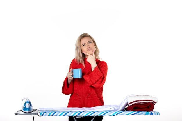 흰색 바탕에 파란색 컵을 들고 다림판 뒤에 서 있는 생각하는 매력적인 젊은 여성의 전면 모습