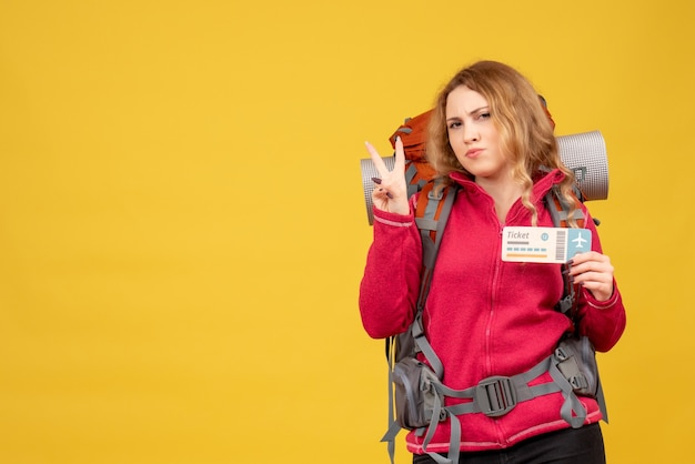 チケットを保持し、勝利のジェスチャーを作る医療マスクで若い旅行中の女の子の正面図