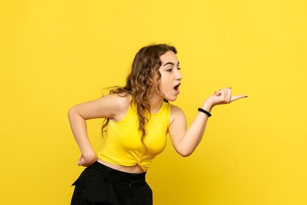 노란색 벽에 주장하는 젊은 여자의 전면보기