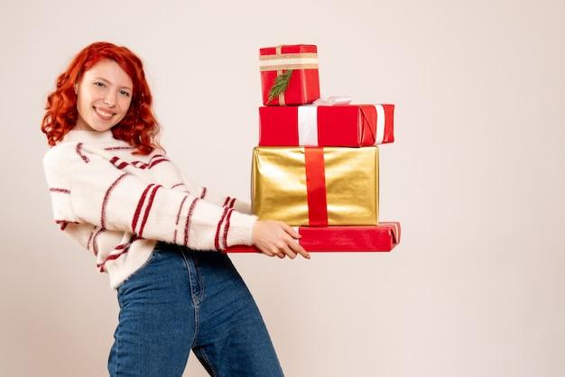 白い壁にクリスマスプレゼントを運ぶ若い女性の正面図