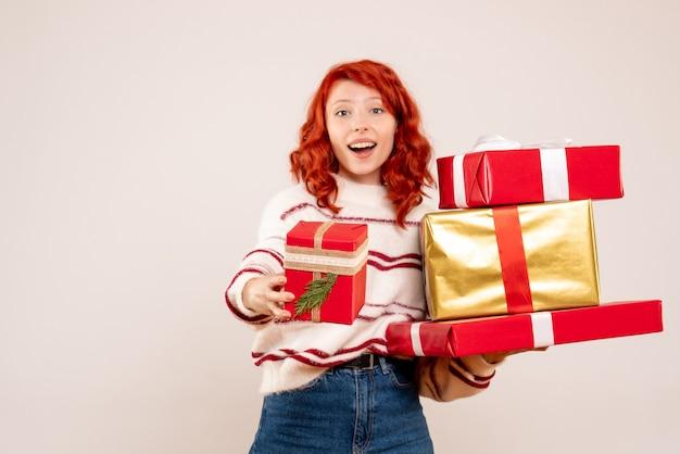 크리스마스를 들고 젊은 여자의 전면보기 흰 벽에 선물