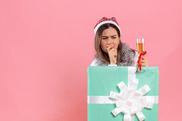 분홍색 벽에 음료와 함께 크리스마스를 축하하는 젊은 여자의 전면보기