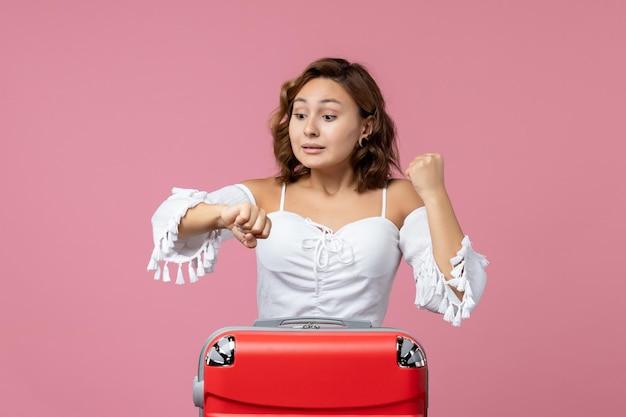 ピンクの壁に興奮した顔で時間をチェックする若い女性の正面図