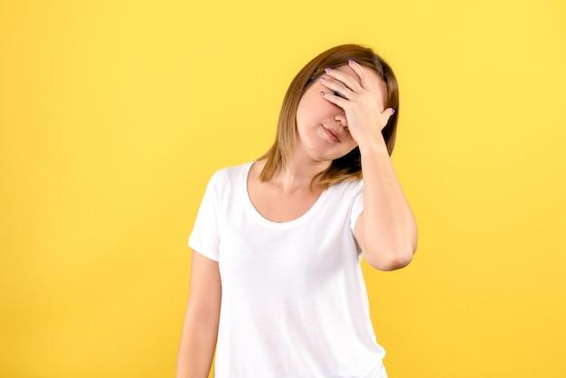 노란색 벽에 그녀의 얼굴을 덮고 젊은 여자의 전면보기
