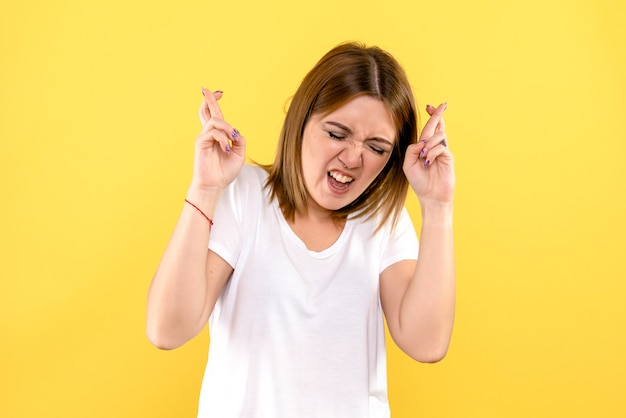 노란색 벽에 젊은 여자 횡단 손가락의 전면보기