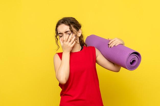 黄色の壁で泣いている若い女性の正面図