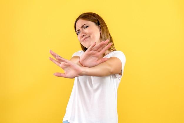 노란색 벽에 불쾌한 젊은 여자의 전면보기