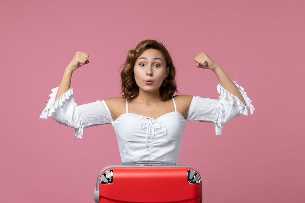 ピンクの壁に感情的にポーズをとって若い女性の正面図