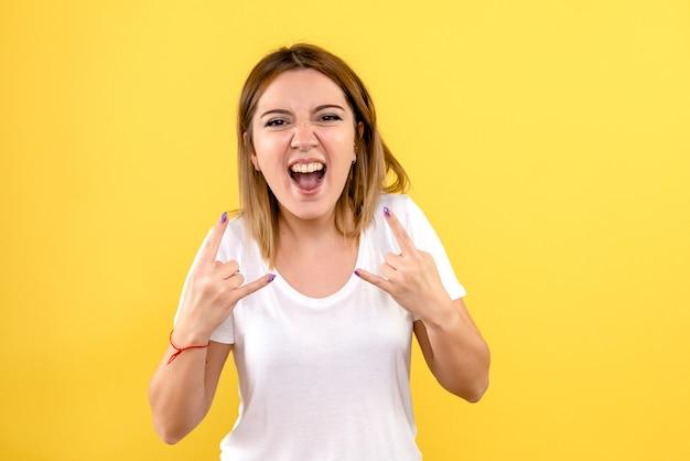 노란색 벽에 감정적으로 기뻐하는 젊은 여자의 전면보기