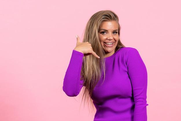 Вид спереди молодой женщины, чувствующей себя счастливой в красивом фиолетовом платье на розовой стене