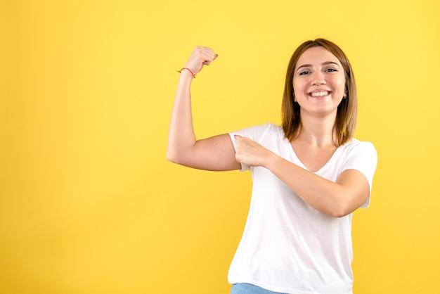 노란색 벽에 flexing 젊은 여자의 전면보기