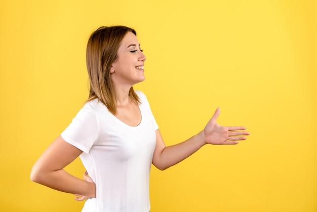 노란색 벽에 누군가 인사하는 젊은 여자의 전면보기