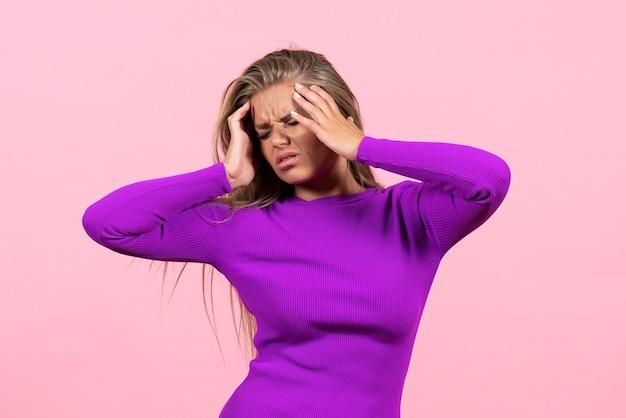 Вид спереди молодой женщины с головной болью в красивом фиолетовом платье на розовой стене