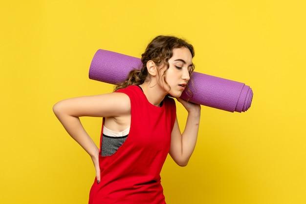 Вид спереди молодой женщины с болью в спине на желтой стене