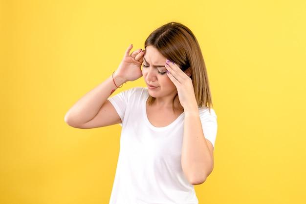 노란색 벽에 두통을 가지고 젊은 여자의 전면보기