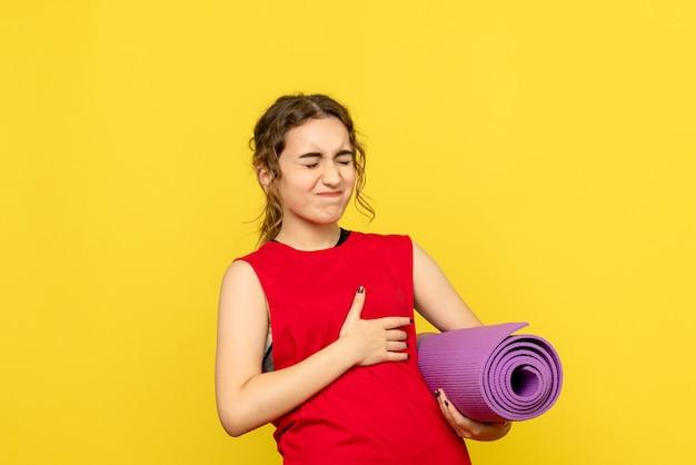Вид спереди молодой женщины с болью в сердце на желтой стене