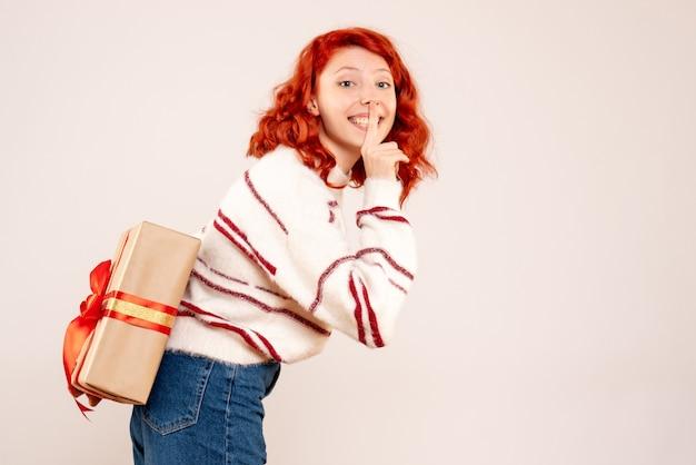 흰 벽에 그녀의 뒤에 크리스마스 선물을 숨기는 젊은 여자의 전면보기