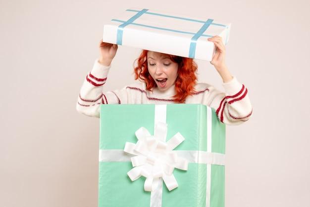 흰 벽에 크리스마스 선물 안에 숨어있는 젊은 여자의 전면보기