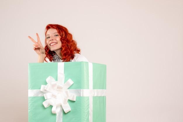 白い壁にプレゼントの中に隠れている若い女性の正面図