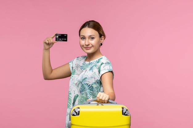 분홍색 벽에 은행 카드를 들고 있는 젊은 여성의 전면 모습